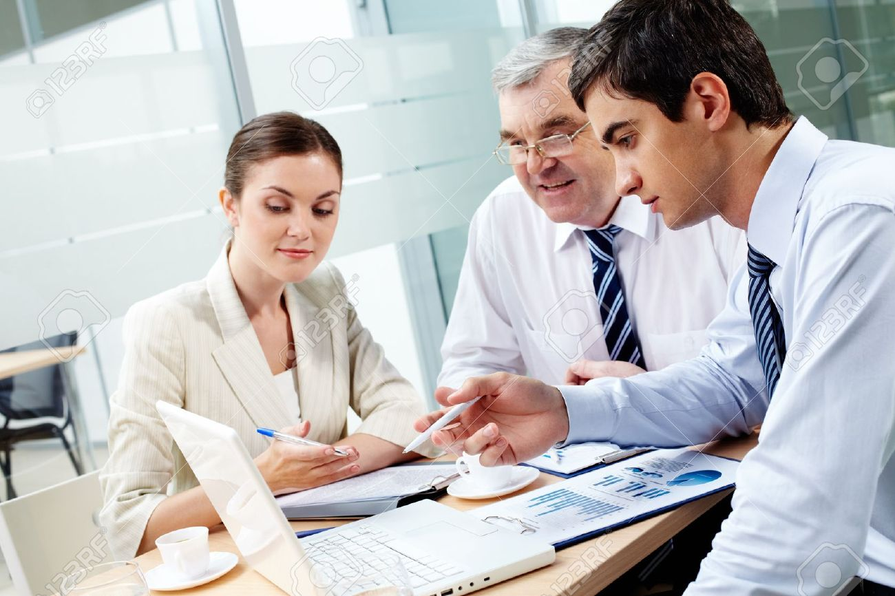12061644-a-business-team-of-three-sitting-in-office-and-planning-work-stock-photo